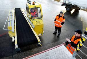 Håkan Andersson övar på att träffa rätt med bagagebandet med hjälp av Arvid Tingelöfs direktiv.