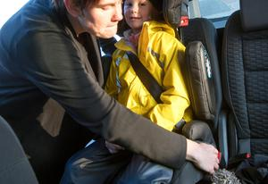 Anna Lindström sätter fast sitt barn Maja i en av stolarna i testet. Bild: Anna Sigge