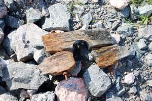 På stranden ligger en träbit med rostiga skruvar.