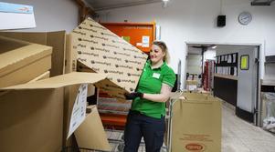 Katarina Fahlén på Coop Eken visar burarna, fullastade med paket, som väntar på att sorteras. I vanliga fall är de i stål, men nu har Postnord fått ta till extra i kartong.