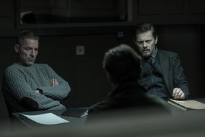 Jonas (Mikael Birkkjær) och Henrik (Thure Lindhardt) gestaltar två olika danska poliser , filmat i den gråtonade ljus som förknippas med en äkta