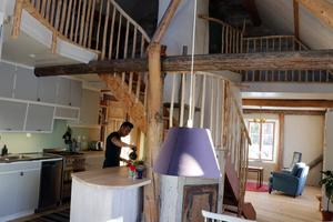 Bottenvåningen har en öppen planlösning med kök, matplats och vardagsrum, med den stora massugnen i mitten av rummet. Här nere finns också parets sovrum och ett badrum.