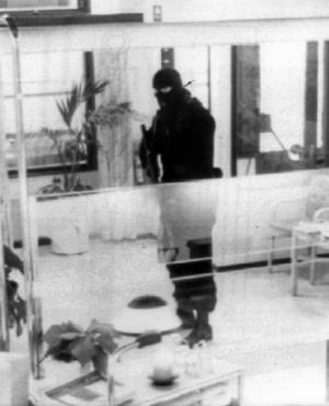 En rånare maskerad i rånarluva och beväpnad med en automatkarbin fotograferad av en övervakningskamera inne på Sparbankens kontor i samband med trippelrånet i Ullared 29:e december 1992 där ett postkontor och Sparbanken samt Föreningsbanken rånades samma dag av fyra personer varav en höll vakt från taket på en skåpbil beväpnad med ett kulsprutegevär. Det visade sig senare att rånen var utförda av Militärligan. Foto: Sparbanken