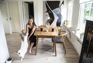 Huset har en öppen planlösning och bakom bordet i köksdelen hänger en av Sofias tavlor.