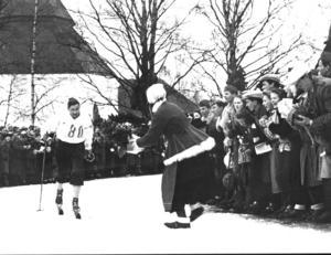 Segerhyllad. Mora-Nisse på väg mot segern i Vasaloppet 1945. Kranskullan Kerstin Sars är beredd att hänga kransen om den suveräne Östnorsåkaren. Foto:Okänd