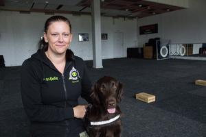 Ann-Sofie Svenman tillsammans med flatcoated retrievern Java i träningslokalen i Kolbäck. Snart ska Java examineras och bli Västmanlands första skogsbrandhund.