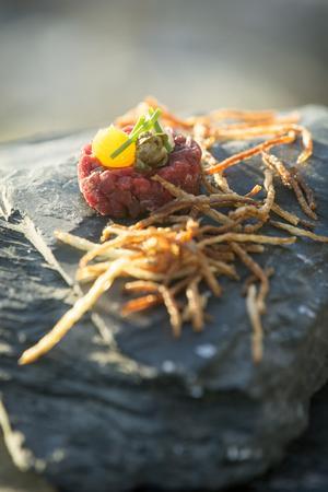 Råbiff med bakad äggula. Strimlorna är fintstrimlad och friterad potatis.