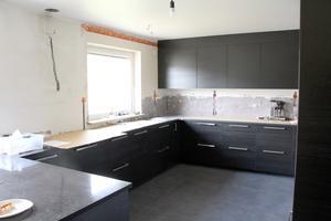 Nytt kök i mörkbrunt trä med plats för mycket matlagning.