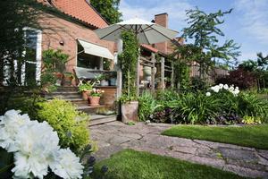 Från sin utbyggda altan har hon utsikt över större delen av sin trädgård.