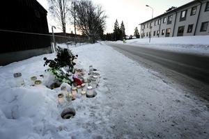 Polisens avspärrningar är borttagna. Det enda som avviker är närvaron av gravljus och frusna blommor i en smutsig snödriva.