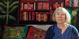 Barbro Ager är omgiven av färgstarka textilier i sitt hem i Långhed, Alfta. Sidentäcken bakom henne kommer även att visas i utställningen.