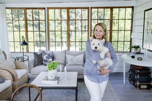 Den senaste utbyggnaden är det inglasade uterummet där gamla fönster ger mycket karaktär.  Här Katarina tillsammans med Sally, familjens hund.