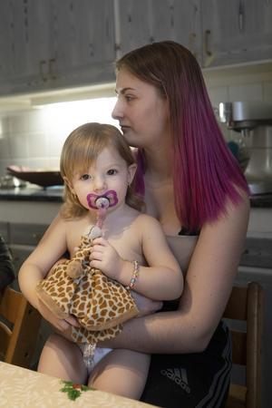 Näst äldst och näst yngst. Minnah, 2 år, kommer till storasyster Jonna, 15 år, för att få få en kram och mysa lite.