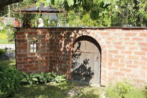 Den teglade muren var Curt Fernros idé. Dörren är gjord av ena sonens gamla altantrall och stenarna kommer från ett rivningsobjekt.