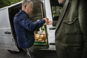 En hjälparbetare delar ut gratis mat vid parken Jardin Anaïs-Nin.