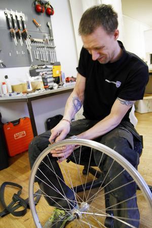 Stefan Källman som driver Cykelverkstaden, byter slang på grund av en punktering.