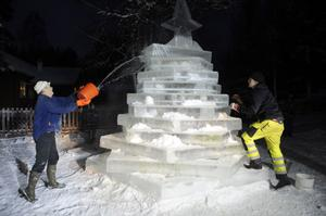 Ove Persson häller på vatten för att isblocken ska frysa samman medan John Persson murar med snö.