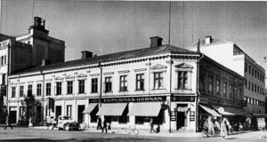 År 1952 tog fotografen Carl Larsson denna bild från Stortorget i Gävle. Den visar hörnet Drottninggatan-Norra Kansligatan, där Ekiperingshörnan höll till. Observera den gamla lastbilen till vänster, en raritet i dag.