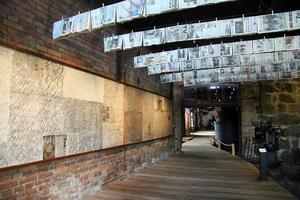 Forntida meddelande kallar Ulla Viotti de blyertsfrottage hon gjort av Ockelbostenen. De sitter på väggen till vänster. I taket Samtida meddelande, av dagstidningar.