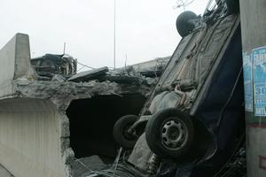 En bil som ramlat ned i ett hål i en betongkonstruktion på morotvägen i Santiago.
