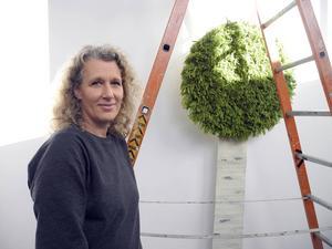 Åsa Åkerström arbetar med hängningen av sitt träd som visas på Magasinet.