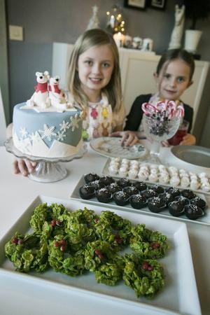 Äntligen dags att provsmaka! Amanda och Emma framför julgodisbordet. På bordet ses också mamma Thereses fina vintertårta.