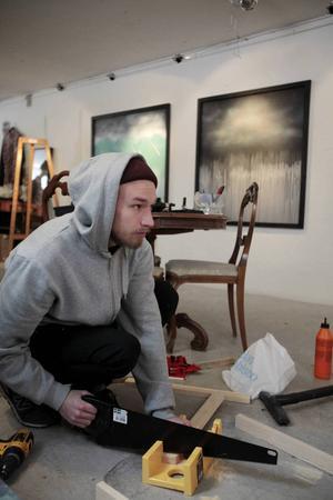 Henrik Ljusberg bygger tavelramar inför en utställning på Urbn Arts.