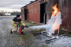 Det övertända träbålet släcks på ett par sekunder när brandmannen Mårten Lundin attackerar med släckaren.