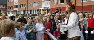 Celine Estassy, iklädd Flower power-kläder, ledde sången på skolgården.