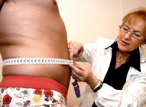 Mai-Lis Hellénius, professor i allmänmedicin vid Karolinska Institutet, mäter en manlig patients mage: har man över 94 cm är man i riskzonen.