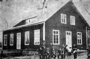 Ett foto på den snickerifabrik Knuts Magnus Eriksson startade i Solvarbo och vars maskiner drev av elektricitet alstrad i den egenhändigt byggda kraftstationen dit folk kom i skaror för att beskåda nymodigheterna. Vid fabriken arbetade tidvis ett 30-tal anställda innan tillverkningen lades ned och huset kom att använda som biograf och danssalong. Huset revs 1922.