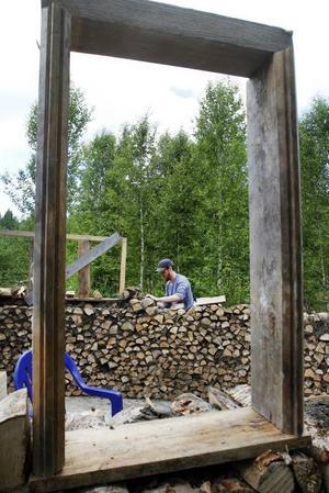 Genom det som ska bli ett fönster på lerhuskapellet ser man Hannes Rydell som murar kapellet.