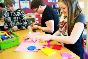 Fredrik och Matilda får hjälp av läraren Mariah att göra bokmärken med hjälp av cirklar och rektanglar.