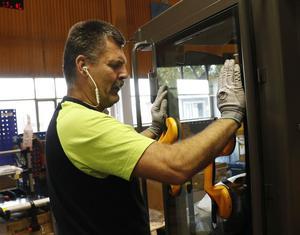 """Urban Rosén monterar rutor på en förarhytt. När rutan sitter på plats måste limmet härda i tolv timmar. Han tillhör veteranerna på företaget. """"Nästa år har jag jobbat här i 40 år"""", konstaterar han."""