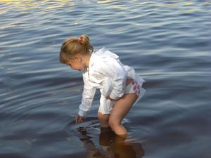 Jag är ingen van fotograf, men här blev det en fin bild, när mitt barnbarn Malin (Lindström) känner på vattnet vid den lilla badplatsen vid Borgåsund.
