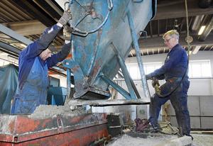 Torbjörn Olsson och Kjell Österholm hjälps åt med att fylla en form som ska bli en stödmur vid en ny återvinningsstation i Brunflo.