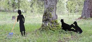 Eva Klingberg har adderat en kvinnas svarta silhuett till den tidigare skulpturen av hennes make som vilar mot en trädstam.