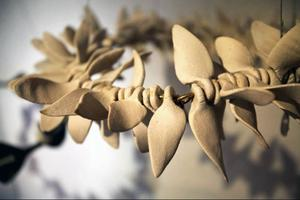"""Små propellrar eller rentav skelettdelar? Kanske en krans flätad av ryggkotor? Bibbi Forsmans keramik på Drejeriet leker med former och symboler under rubriken """"I glädje och sorg""""."""