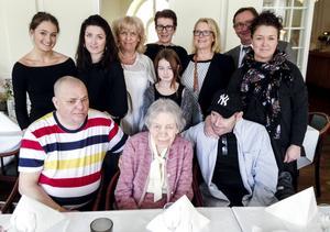 Sittandes i mitten med släktingar runtom sitter födelsedagsbarnet Karin Forsberg som går in på tresiffrigt.