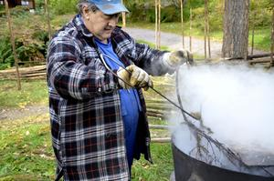 Håller grytan kokande. Vidjor av gran kokas av Lennart Sandberg för att bli mjuka så att man kan vrida dem runt störarna.