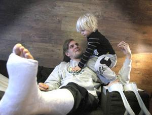 Joel Asp får hålla sig hemma med familjen under skadefrånvaron. Här i sjuksoffan med sonen Liam, 3.