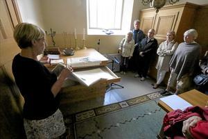 Sakristia. Kyrkguiden Eva Wetter visar dukarna med liljor i sakristian på Hackvads kyrka.