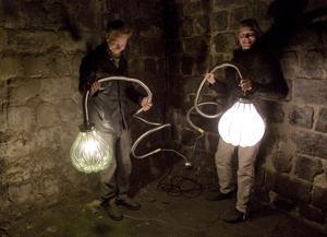 Elna Jolom (till höger) får hjälp att sätta glaslamporna på plats i masugnen.