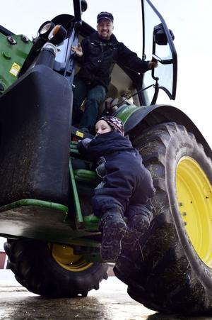 Elias kämpar sig upp till pappa i traktorn.