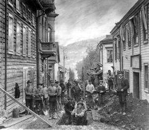 Den här bilden är troligen tagen 1892 eller 1983 då Skånska Cementgjuteriet byggde vatten- och avloppsledningar i Östersund. 19 jobbare gräver sig fram längs Residensgränd i Östersund för här ska en dagvattenledning läggas ner. Fotografen skulle kunna ha varit en man vid namn Olsson. Han hade vid tiden en fotoateljé i huset till höger.