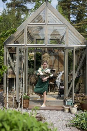 Linda Hansson framför sitt nya växthus. Det står på samma plats  som det förra men är betydligt högre.
