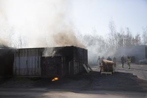 Det brinner i ett 20-tal sammanlänkade containrar. Därinne finns åtta personer som behöver hjälp ut.