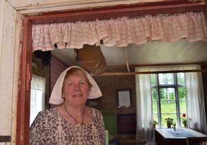 Land Alice i en dörröppning i hennes faluröda fäbodstuga – med brödkakor i taket och pelargoner i fönstren.