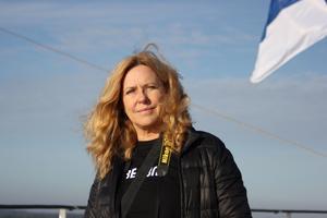 Eija Salminen mellan Sverige och Finland, under finska flaggan. Foto: Neea Muikku.