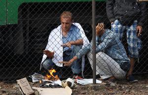 Män bränner papper för att värma sig utanför ett tåg som stoppats i Bicske.